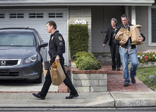Police investigators take away evidence from the home of the mother of fugitive suspect former Los Angeles police officer Christopher Dorner, in La Palma, Calif., on Friday, Feb. 8, 2013. Police agenc