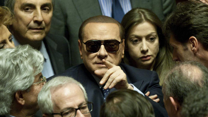 "Former Italian Premier Silvio Berlusconi wears sunglasses as he attends the vote operations at the Senate, in Rome Saturday, March 16, 2013. Berlusconi was met with jeers from protesters as he arrived to take part in the Senate vote, a day after leaving a Milan hospital following a week's treatment for an eye inflammation. Before entering the Senate building, he turned to the protesters and said ""shame on you."" Berlusconi has been seeking to have two trials — a tax fraud appeal and a sex-for-hire hearing — postponed due to the eye condition. The courts responded by dispatching court-appointed doctors to verify its severity. (AP Photo/Mauro Scrobogna) ITALY OUT"