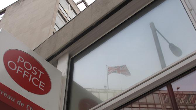 """A British flag flying atop Scotland Yard's London headquarters is reflected in the windows of the Broadway Post Office on Friday, April 27, 2012, in central London.  Police said Friday the post office was the unlikely site of the arrest of 49-year old Gianfranco Techegne, an Italian fugitive wanted over the killing of an officer in Naples, Italy, three decades ago. The British police said they were """"acting on intelligence"""" to detain the fugitive wanted by Italian police since 1982 in connection with the armed robbery of a car rental agency in Naples during which a young police officer was fatally wounded. (AP Photo/Raphael Satter)"""