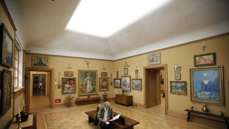 """A visiter sits in gallery 18 during a preview of The Barnes Foundation Wednesday, May 16, 2012, in Philadelphia. After years of bitter court fights, the Barnes Foundation is scheduled to open its doors to the public on May 19 at its new location on Philadelphia's """"museum mile."""" (AP Photo/Matt Rourke)"""