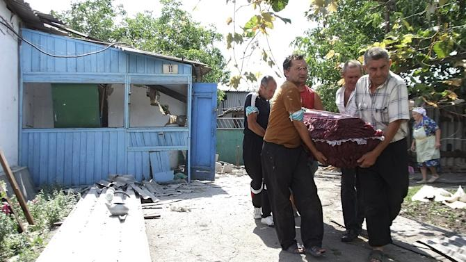 Men carry a coffin, containing one of two victims of an early morning shelling according to locals, outside a damaged house before a funeral in Donetsk