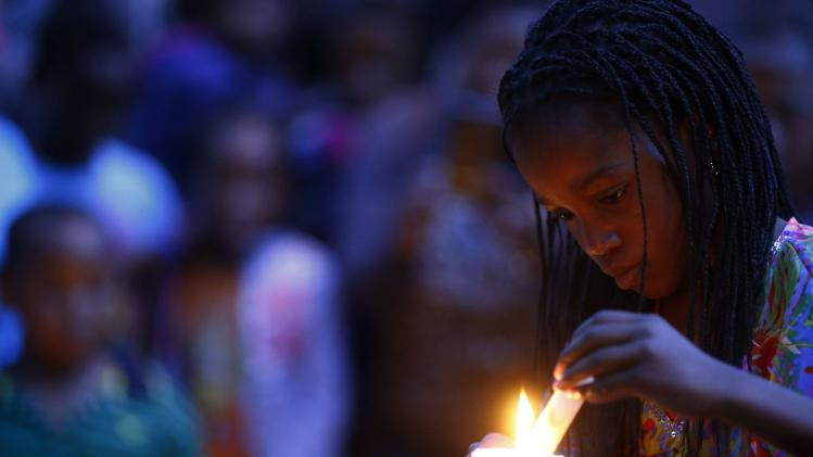 A girl relights candles outside the house where Nelson Mandela died in Johannesburg