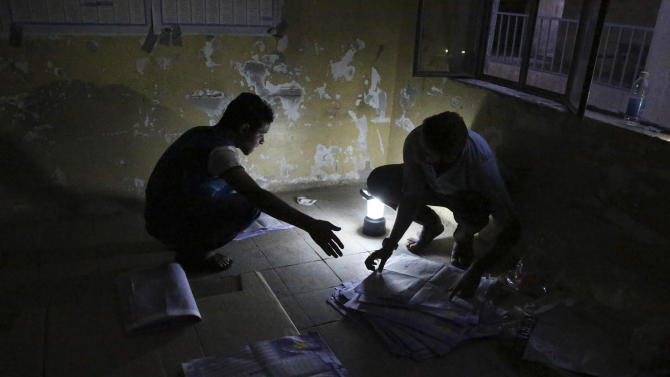 Electoral workers count ballots under lamplight, due to a power cut, as polls close at a polling center in Baghdad, Iraq, Wednesday, April 30, 2014. Iraqis braved the threat of bombs and other violence to vote Wednesday in parliamentary elections amid a massive security operation as the country slides deeper into sectarian strife. (AP Photo/Karim Kadim)