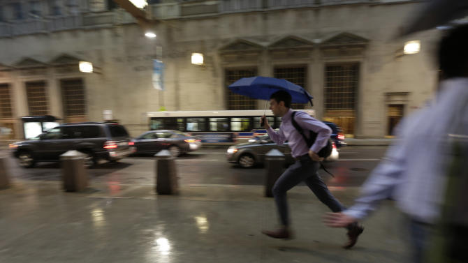 A pedestrian races to avoid an unusually massive line of storms packing hail, lightning and tree-toppling winds that have been forecast for evening rush hour, Wednesday, June 12, 2013, in Chicago. (AP Photo/M. Spencer Green)