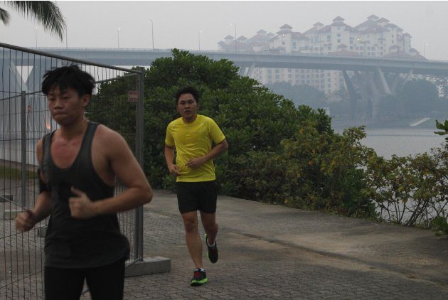 People jog past the hazy skyline of the Tanjong Rhu residential area in Singapore