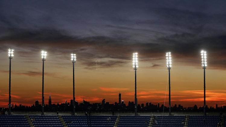 The skyline of the borough of Manhattan can be seen in the distance as fans wait for Roger Federer, of Switzerland, and Sam Groth, of Australia, to play during the second round of the U.S. Open tennis tournament Friday, Aug. 29, 2014, in New York. (AP Photo/Darron Cummings)