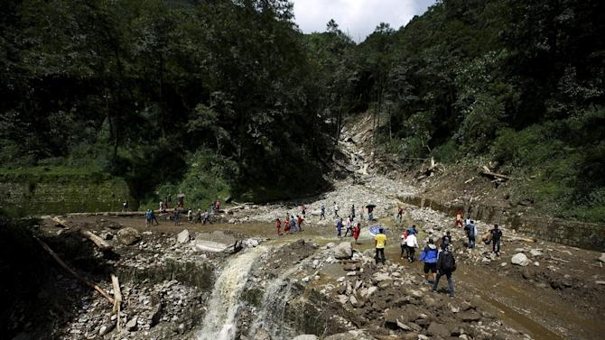 People walk along a blocked highway after a landslide at Lumle village