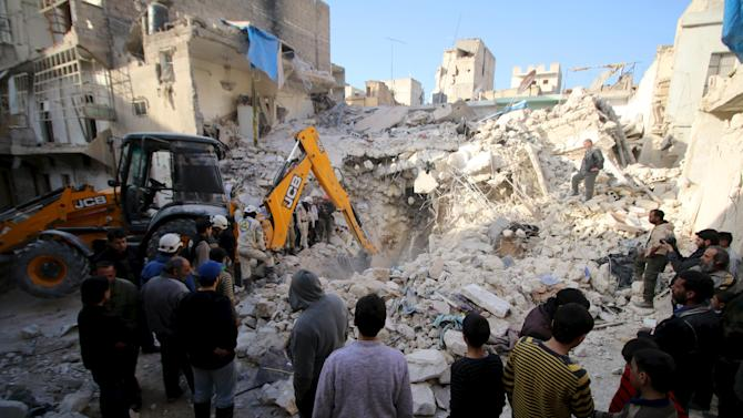 Civil defence members search for survivors after airstrikes by pro-Syrian government forces in the rebel held al-Qaterji neighbourhood of Aleppo