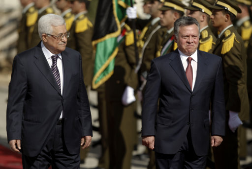 King Abdullah II of Jordan, right, and Palestinian President Mahmoud Abbas, walk past honor guards prior to their meeting in the West Bank city of Ramallah, Thursday, Dec. 6, 2012. Jordan's King Abdullah II has begun a brief visit to the West Bank in support of Palestinian President Mahmoud Abbas' successful bid for U.N. recognition of a state of Palestine. (AP Photo/Majdi Mohammed)