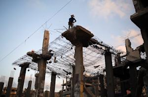 Palestinian workers remove the rubble of a building…