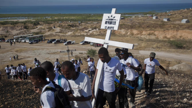 Relatives of those who died in the 2010 earthquake walk in single file to place a cross on a hilltop to remember those who died in the devastating earthquake, prior to a memorial service at Titanyen, a mass burial site north of Port-au-Prince, Haiti, Saturday, Jan. 12, 2013. Haitians recalled the tens of thousands of people who lost their lives in a the 7.0 magnitude earthquake three years ago, marking the disaster's anniversary Saturday with a simple ceremony. Haiti's previous presidential administration said 316,000 people were killed but no one really knows how many died.  (AP Photo/Dieu Nalio Chery)