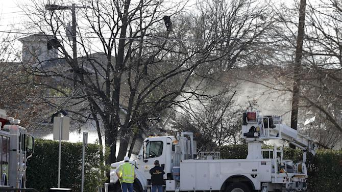 Spray from fire fighters water hoses and smolder rises off the top of the remains of a structure as a fire investigator and another person check out the scene Friday, Jan. 11, 2013, in Lewisville, Texas. An explosion Friday in a North Texas neighborhood leveled a home that is part of a local nonprofit's affordable housing program, injuring at least three men and scattering debris.(AP Photo/Tony Gutierrez)