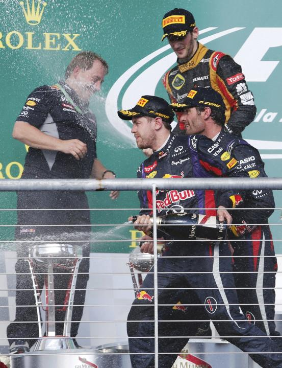 Sebastian Vettel of Germany, Mark Webber of Australia and Romain Grosjean of France spray champagne next to Matt Cadieux during celebrations on the podium after the Austin F1 Grand Prix at the Circuit