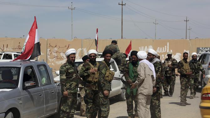 In this photo taken Friday, March 27, 2015, Shiite militiamen, wearing turbans, prepare with Iraqi security forces before deploying to fight against Islamic State group extremists in Tikrit, 130 kilometers (80 miles) north of Baghdad, Iraq. On the ground, the Iraqi troops pressed their push in the city on Friday as fighter planes pounded IS targets from above. Militants holed up in the center of Tikrit fired mortars at the military, slowing its progress despite the new aerial campaign. (AP Photo/Khalid Mohammed)