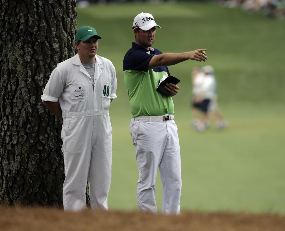 Marc Leishman, of Australia, discusses his shot with his caddie Matthew Kelly in the rough off the 17th fairway during the first round of the Masters golf tournament Thursday, April 11, 2013, in Augusta, Ga. (AP Photo/David J. Phillip)