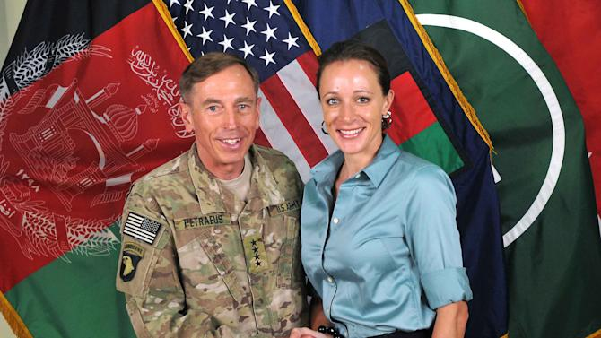 "FILE -- This July 13, 2011, photo made available on the International Security Assistance Force's Flickr website shows the former Commander of International Security Assistance Force and U.S. Forces-Afghanistan Gen. Davis Petraeus, left, shaking hands with Paula Broadwell, co-author of  ""All In: The Education of General David Petraeus.""  The Justice Department is dropping its investigation of David Petraeus' mistress, Paula Broadwell, into whether she stalked a romantic rival online.  (AP Photo/ISAF)"