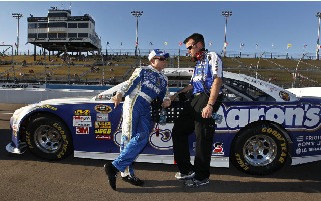 Mark Martin, left, talks with a crew member while leaning on his car after his laps during Sprint Cup qualifying for the NASCAR Subway Fresh Fit 500 auto race on Friday, March 1, 2013, in Avondale, Ar