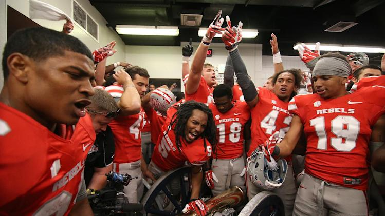 UNLV celebrates around the Fremont Cannon in the locker room following an NCAA football game against Nevada in Reno, Nev., on Saturday, Oct. 26, 2013. UNLV defeated Nevada 27-22