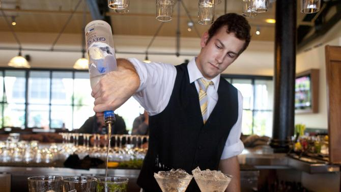 In this photo taken Monday, Nov. 19, 2012, bartender Nico Reynders makes three different drinks from vodka at the Bistro Boudin in San Francisco. Booze with multiple personalities, like the best kind of party guests, can adapt to the situation and provide a festive little home bar that adds panache to your holiday party. (AP Photo/Eric Risberg)
