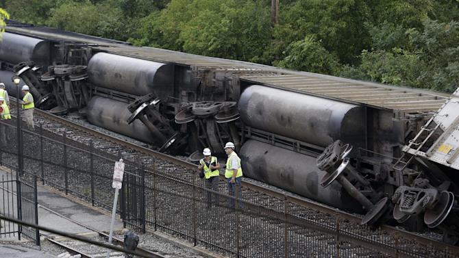 Officials stand near part of a CSX freight train that derailed overnight in Ellicott City, Md., Tuesday, Aug. 21, 2012. Authorities said two people not employed by the railroad were killed in the incident. (AP Photo/Patrick Semansky)