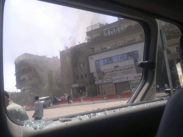 This citizen journalist image shot through a broken car window shows smoke billowing from a building after fighting between rebels and Syrian troops in the Yarmouk camp for Palestinian refugees in south Damascus, Syria, Saturday, July 21, 2012. This week, fierce fighting between troops and rebels reached the Syrian capital, the central bastion of Bashar Assad's rule, shattering parts of the city and sending thousands of people fleeing to neighboring Lebanon and Iraq. Activists and residents reported a tense calm in Damascus Saturday but said sporadic gunfire and explosions could be heard throughout the night. (AP Photo)