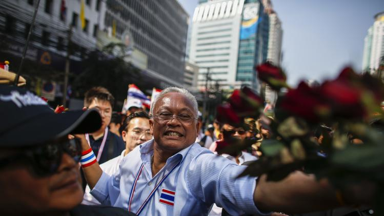 Anti-government protest leader Suthep Thaugsuban receives flowers from his supporters during a rally at a major business district in Bangkok