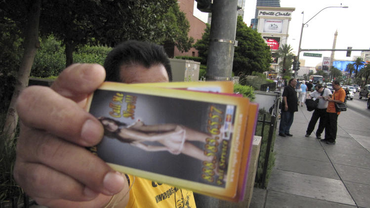 """An unidentified man on a Las Vegas Strip sidewalk hands out cards advertising exotic dancers on Wednesday, Aug. 29, 2012. Las Vegas officials have passed a litter ordinance requiring such """"handbillers"""" to pick up after tourists who drop the materials. The American Civil Liberties Union says the new ordinance might violate free speech protections. (AP Photo/Mead Gruver)"""