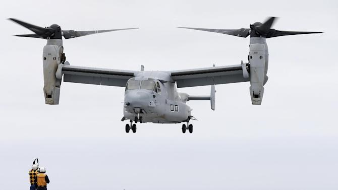 A Marine MV-22 Osprey aircraft lands on the Japanese destroyer JS Hyuga Friday, June 14, 2013, in coastal waters off San Diego. The aircraft made an unprecedented landing on the vessel Friday, despite protests in Japan over concerns over the tilt-rotor aircraft's safety record. (AP Photo/Gregory Bull)