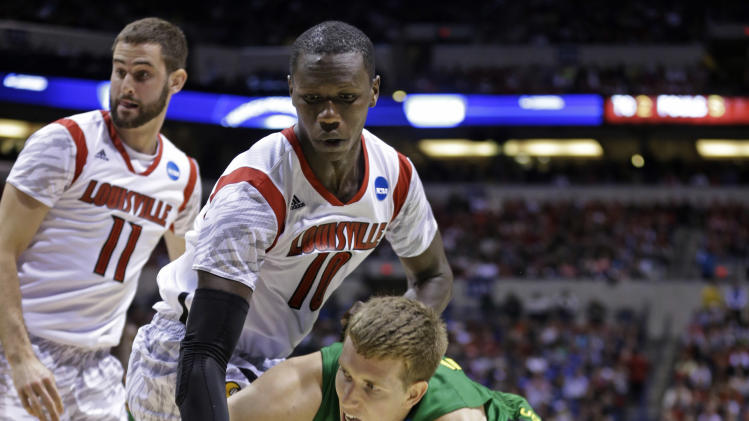 Oregon forward E.J. Singler passes the ball around Louisville center Gorgui Dieng (10) during the second half of a regional semifinal in the NCAA college basketball tournament, Friday, March 29, 2013, in Indianapolis.  Louisville won 77-69. (AP Photo/Michael Conroy)