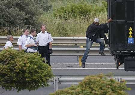 French policemen ask a migrant to get out of the trailer of a truck as lorries wait on a road which leads to the Channel Tunnel terminal in Coquelles near Calais