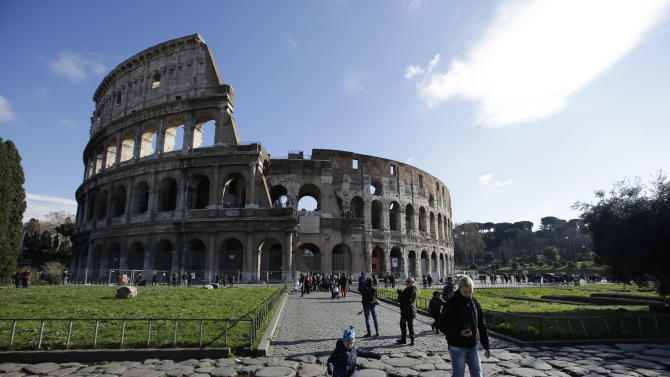 Tourists walk outside Rome's Colosseum, Friday, Jan. 18, 2013. A long-delayed restoration of the Colosseum's only intact internal passageway has yielded ancient traces of red, black and blue frescoes — as well as graffiti and drawings of phallic symbols — indicating that the arena where gladiators fought was far more colorful than previously thought. Officials unveiled the discoveries Friday and said the passageway would be open to the public starting this summer, after the €80,000 ($100,000) restoration is completed. The frescoes were hidden under decades of calcified rock and grime, and were revealed after the surfaces were cleaned. The traces confirmed that while the Colosseum today is a fairly monochrome gray travertine rock, red brick and bits of moss-covered marble, in its day its interior halls were a rich and expensive Technicolor. (AP Photo/Gregorio Borgia)
