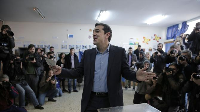 Alexis Tsipras, leader of Greece's Syriza left-wing main opposition party surrounded by photographers reacts as he casts his vote at a polling station in Athens, Sunday, Jan. 25, 2015. Greeks were voting Sunday in an early general election crucial for the country's financial future, with the radical left Syriza party of Alexis Tsipras tipped as the favorite to win, although possibly without a large enough majority to form a government. (AP Photo/Lefteris Pitarakis)