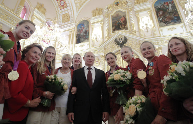 Russian President Vladimir Putin, center, poses for a picture with the national synchronized swimming team during an awards ceremony for Russia's Olympians in Moscow's Kremlin on Wednesday, Aug. 15, 2012. (AP Photo/Maxim Shemetov, Pool)