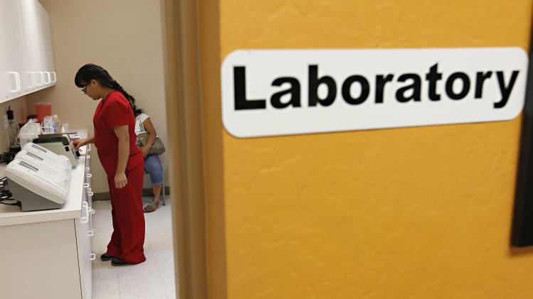Lab technician Sara Rodriguez works in the lab at Wesley health Center for uninsured patients, Wednesday, May 1, 2013, in downtown Phoenix. President Barack Obama has championed two sweeping policy changes that could transform how people live in the United States: affordable health care for all and a path to citizenship for the 11 million immigrants illegally in the country. But many immigrants will have to wait more than a decade to qualify for health care benefits under the proposed immigration overhaul being debated by Congress, ensuring a huge swath of people will remain uninsured as the centerpiece of Obama's health care law launches next year. (AP Photo/Matt York)