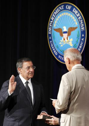 Secretary of Defense Leon Panetta, left, raises his right hand during a ceremonial swearing in with Vice President Joe Biden, right, as his wife Sylvia Panetta holds a Bible at the Pentagon, Friday, July 22, 2011 in Washington. (AP Photo/Alex Brandon)
