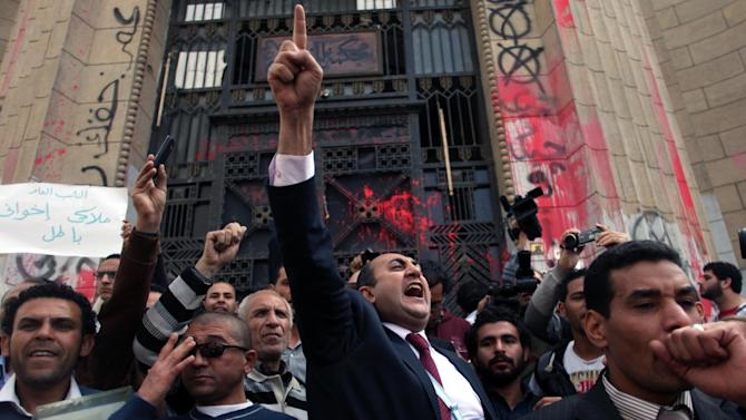 Former presidential candidate Khaled Ali, center, chants slogans during a protest in front of the general prosecutor's office in Cairo, Egypt, Tuesday, March 26, 2013, a day after the prosecutor general ordered the arrest of a prominent blogger and four others for allegedly instigating violence with comments posted on social media. The charges stem from clashes between supporters and opponents of the country's Islamist president last week that left 200 injured.  (AP Photo/Khalil Hamra)
