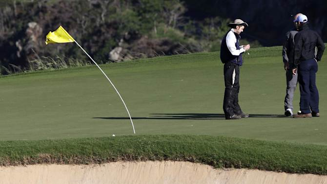 The flag on the 11th green bends in the wind as a television crew stands nearby before the Tournament of Champions PGA golf tournament on Sunday, Jan. 6, 2013, in Kapalua, Hawaii. Play was to have started two days earlier but was delayed because of rain and high winds. (AP Photo/Elaine Thompson)