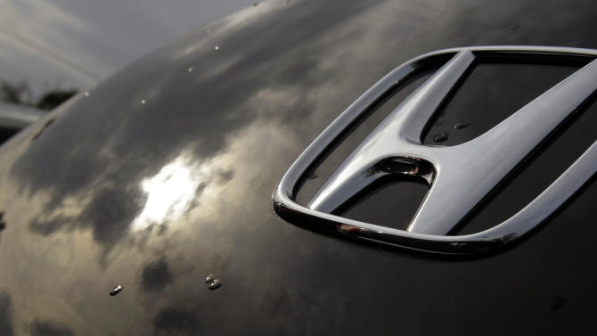 In this Oct. 5, 2012, photo, a sunset is reflected in a Honda vehicle in Chicago. Major automakers are reporting Thursday, Nov. 1, 2012, that sales increased for October despite losing three days of business to the punishing rain and wind from superstorm Sandy.  (AP Photo/Nam Y. Huh)