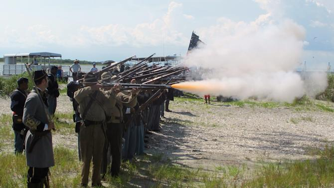 """Re-enactors representing both North and South fire a volley on Morris Island near Charleston, S.C., on Thursday, July 18, 2013 during a observance of the 150th anniversary of the charge of the black 54th Massachusetts Volunteer Infantry in a fight commemorated in the film """"Glory."""" (AP Photo/Bruce Smith)"""