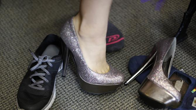A girl tries on stilettos at an event that provides free prom dresses, shoes and accessories to 70 homeless and low income school girls from the Assistance League of Los Angeles in Los Angeles