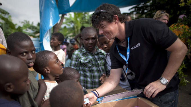 FILE - In this June 6, 2011 file photo, Rory McIlroy distributes bars of soap to children at a kindergarten run by UNICEF in Port-au-Prince, Haiti. McIlroy wants to help children around the world through a foundation and on his golf bag. On Thursday, Jan. 10, 2013, McIlroy announced he has started The Rory Foundation. Among the first projects is to bring attention to children by putting the name of charities on his bag when possible. (AP Photo/Ramon Espinosa, File)