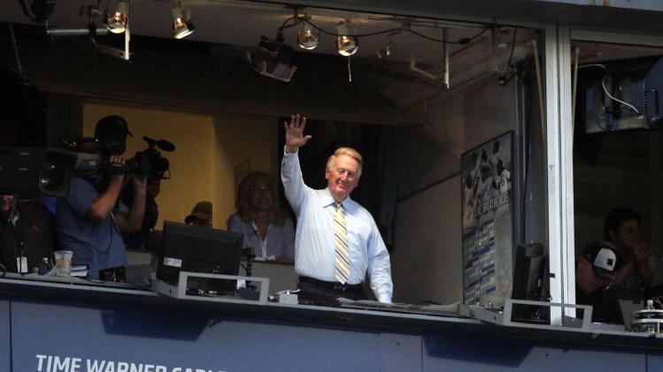 Broadcaster Vin Scully acknowledges the crowd at Dodger Stadium during a baseball game between the Los Angeles Dodgers and the Atlanta Braves on Tuesday, July 29, 2014, in Los Angeles. The Dodgers announced that Scully will remain with the team for the 2015 season. (AP Photo/Jae C. Hong)