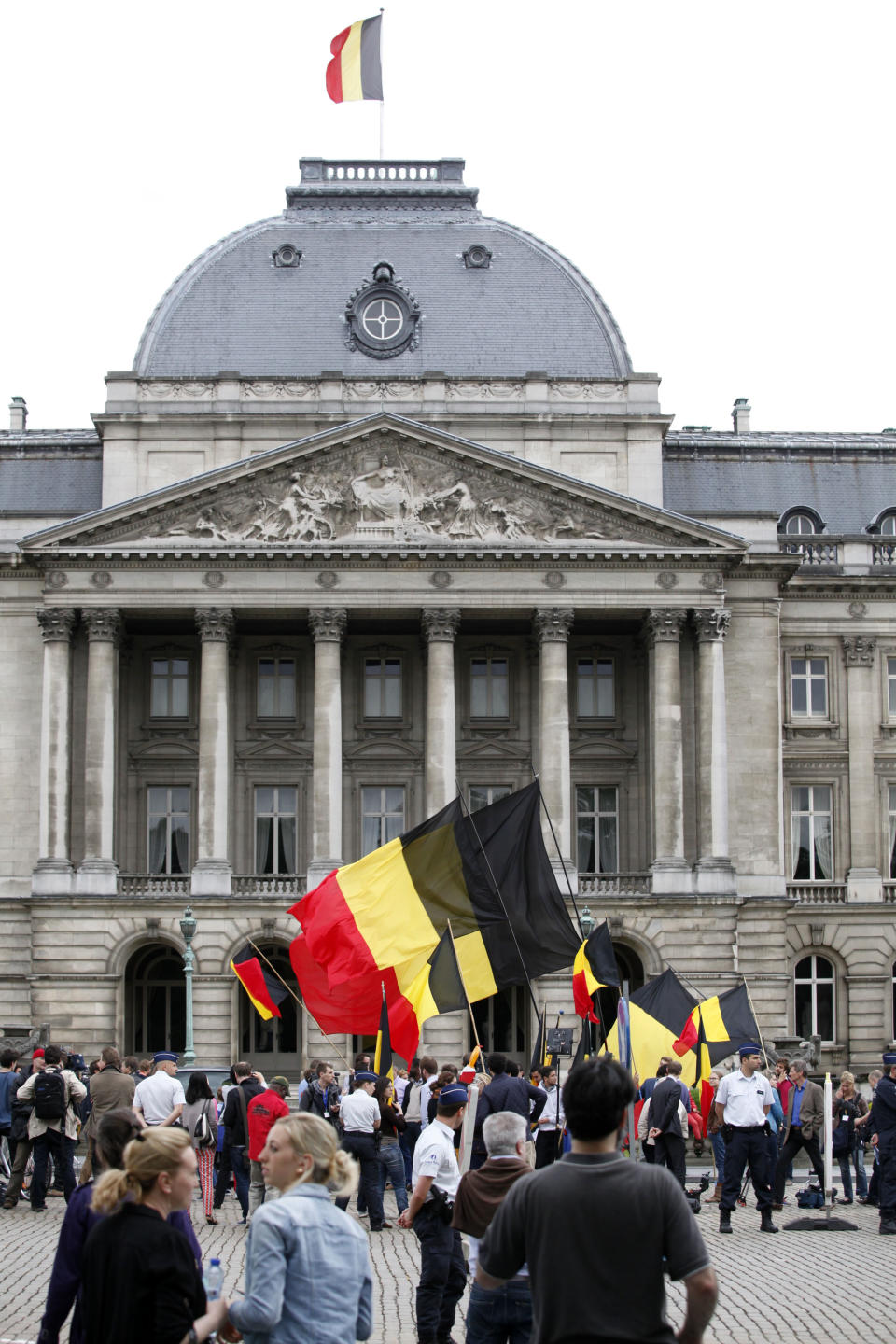 People wave Belgian flags in front of the Royal Palace downtown Brussels, Wednesday, July 3, 2013. Belgian King Albert has unexpectedly announced that he will step down in favor of his son, Crown Prince Philippe. on July 21, 2013. (AP Photo/Francois Walschaerts)