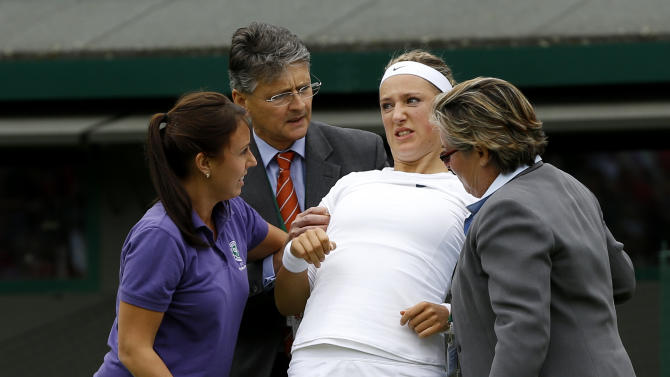Victoria Azarenka of Belarus, second from right, is helped up after taking a fall during her Women's first round singles match against Maria Joao Koehler of Portugal at the All England Lawn Tennis Championships in Wimbledon, London, Monday, June 24, 2013. (AP Photo/Kirsty Wigglesworth)