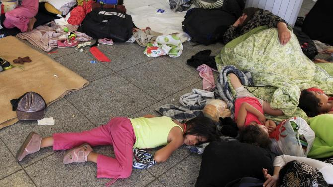 Children sleep on the floor as their families wait for a train to Austria at the railway station in Budapest