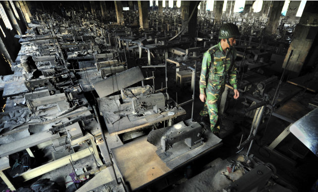A Bangladeshi police officer walks between rows of burnt sewing machines in a garment factory outside Dhaka, Bangladesh, Sunday, Nov. 25, 2012. At least 112 people were killed in a late Saturday night