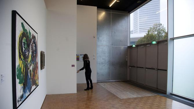 The exit doors used to get seven stolen paintings out of Kunsthal museum are seen next to a painting by Karel Appel, at the museum in Rotterdam, Wednesday Oct. 17, 2012. Police investigating a multimillion euro (dollar) art heist say they are following up several tips from the public, a day after thieves grabbed seven paintings from the walls of a Rotterdam gallery and vanished into the night. A spokeswoman for detectives on the case, Willemieke Romijn, said Wednesday they have some 15 tips from the public, following a late-night, nationally televised appeal for witnesses to the theft from the Kunsthal gallery of works by celebrated artists including Pablo Picasso, Claude Monet and Henri Matisse. (AP Photo/Peter Dejong)