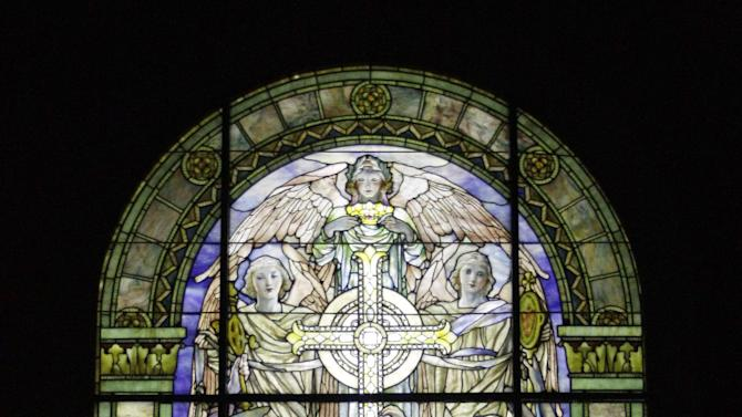 "In this Thursday, Oct. 25 2012 photo, ""The Righteous Shall Receive a Crown of Glory,"" Brainard Memorial Window for Methodist Church, Waterville, New York, ca. 1901 is on display at the ""Louis C. Tiffany and the Art of Devotion"" exhibit at the Museum of Biblical Art in New York.  (AP Photo/Mary Altaffer)"