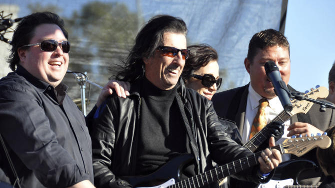 Chuck Brennan, left, majority owner of Dollar Loan Center, and heavy metal icon Alice Cooper, center, kick off a 6,000-square-foot rock ëní roll academy will be open exclusively to the area's 250 Boys & Girls Clubs members, Wednesday, Oct. 10, 2012, in Sioux Falls, S.D. (AP Photo/Dirk Lammers)