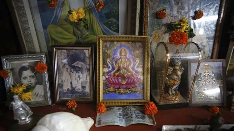 An Indian rupee currency note is seen next to the portrait of the Hindu Goddess of wealth Laxmi inside a shop in Mumbai August 21, 2013.
